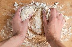 Equipaggi le mani del ` s che producono la pasta, preparante il pane, pizza sul fondo di legno marrone Processo di cottura - l'uo Fotografia Stock Libera da Diritti