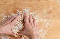 Equipaggi le mani del ` s che producono la pasta, preparante il pane, pizza sul fondo di legno marrone Processo di cottura - l'uo Immagini Stock
