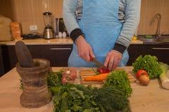 Equipaggi le mani del ` s che tagliano il pepe, dietro gli ortaggi freschi Cuoco maschio alla cucina Immagine Stock Libera da Diritti