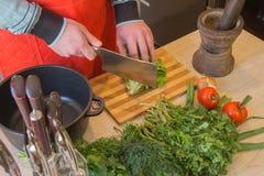 Equipaggi le mani del ` s che tagliano il pepe, dietro gli ortaggi freschi Cuoco maschio alla cucina Fotografia Stock Libera da Diritti