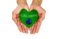 Equipaggi le mani del ` s che tengono la foglia verde a forma di cuore con riscaldamento globale della lettera e della terra su f Fotografie Stock
