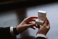 Equipaggi le mani del ` s che tengono una scatola bianca con fedi nuziali Immagine Stock Libera da Diritti