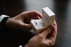 Equipaggi le mani del ` s che tengono una scatola bianca con fedi nuziali Immagini Stock