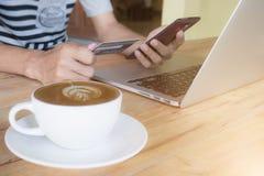 Equipaggi le mani facendo uso della carta di credito del computer portatile e della tenuta dello smartphone con la s Fotografia Stock