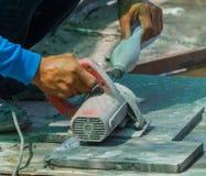 Equipaggi le mattonelle di taglio del lavoratore con la sega circolare e tenga il bottl di plastica Fotografia Stock Libera da Diritti