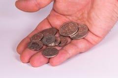 Equipaggi le monete svizzere della tenuta della mano del ` s su un fondo bianco Fotografia Stock
