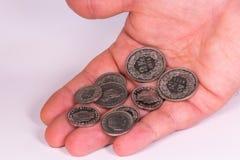 Equipaggi le monete svizzere della tenuta della mano del ` s su un fondo bianco Fotografia Stock Libera da Diritti