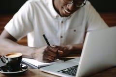 Equipaggi le note di scrittura che si siedono ad una caffetteria con un computer portatile sul fotografie stock libere da diritti