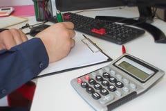 equipaggi le note di scrittura dal computer sulla tavola di legno Equipaggi la mano con la penna, il calcolatore ed il computer s Immagini Stock