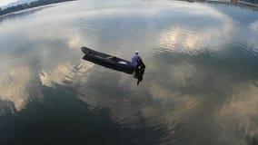 Equipaggi le pagaie la sua barca di legno sul lago nel pomeriggio siluette archivi video