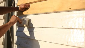 Equipaggi le pitture un pennello con pittura bianca una parete di legno sulla via archivi video