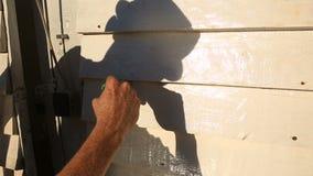 Equipaggi le pitture un pennello con pittura bianca una parete di legno sulla via video d archivio