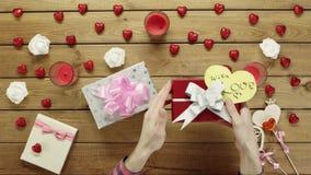 Equipaggi le prove per capire che cosa si trova dentro i suoi regali di festa e li scuote, vista superiore archivi video