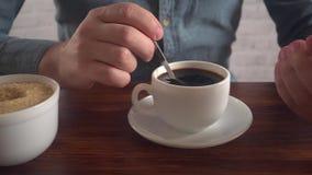Equipaggi le scalpore il suo zucchero in caffè ed esaminare lo smartphone, movimento lento archivi video