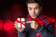 Equipaggi le tenute un regalo in loro mani e mostrilo Immagine Stock
