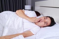 Equipaggi lo sbadiglio e la sua moglie che dormono sul letto Fotografia Stock Libera da Diritti