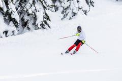 Equipaggi lo sciatore con la macchina fotografica di gopro e del casco sulla sua corsa con gli sci capa Immagine Stock