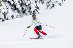 Equipaggi lo sciatore con la macchina fotografica di gopro e del casco sulla sua corsa con gli sci capa Fotografie Stock
