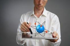 Equipaggi lo scienziato che tiene un PC della compressa con il modello atomico, concetto della ricerca Immagine Stock Libera da Diritti