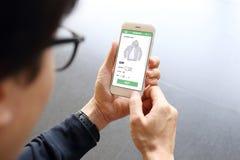 Equipaggi lo smartphone della tenuta con il maglione dell'affare sul sito Web di commercio elettronico Fotografia Stock Libera da Diritti