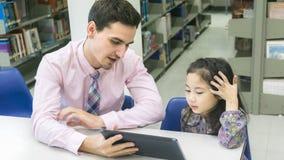Equipaggi lo studente del bambino e dell'insegnante che impara e che considera la compressa devic Fotografia Stock Libera da Diritti
