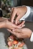 Equipaggi mettere gli anelli sulle mani della sua moglie sul giorno delle nozze fotografia stock