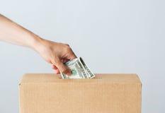 Equipaggi mettere i soldi del dollaro nella scatola di donazione Immagine Stock