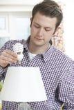 Equipaggi mettere la lampadina di energia bassa nella lampada a casa Immagine Stock