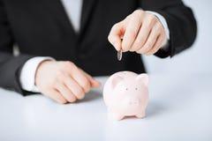 Equipaggi mettere la moneta nel piccolo porcellino salvadanaio Fotografia Stock Libera da Diritti