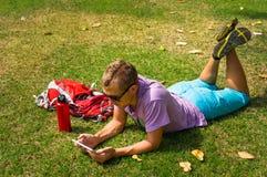 Equipaggi mettere sull'erba e per mezzo della sua compressa Immagini Stock Libere da Diritti