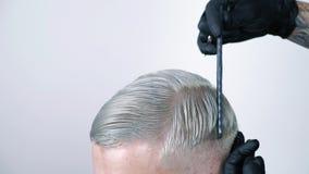 Equipaggi ottenere il taglio di capelli con le forbici di capelli biondi su un fondo bianco archivi video