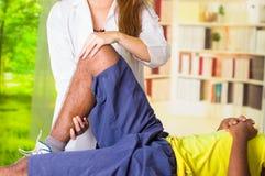 Equipaggi ottenere il trattamento del ginocchio dal fisio terapista, le sue mani che tengono la sua gamba e che applicano il mass Immagini Stock Libere da Diritti