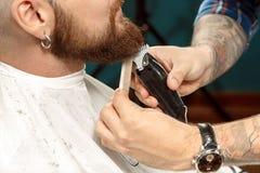 Equipaggi ottenere la sua barba rasa in un negozio di barbiere fotografia stock libera da diritti