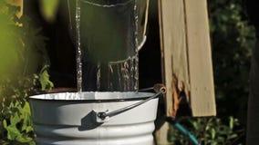 Equipaggi piovere a dirottoe in un'acqua di recente presa del secchio da un pozzo del villaggio alla campagna stock footage