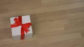 Equipaggi portano il contenitore di regalo bianco con l'arco rosso del nastro e lo mettono sul pavimento Pavimento di legno all'i stock footage