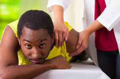 Equipaggi riposarsi ottenendo il trattamento fisico della spalla dal fisio terapista, macchina fotografica esaminante paziente me Fotografia Stock