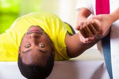 Equipaggi riposarsi ottenendo il trattamento fisico della spalla dal fisio terapista, macchina fotografica esaminante paziente me Immagine Stock Libera da Diritti