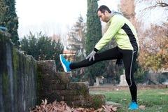 Equipaggi risolvere nel parco della città e l'allungamento dei muscoli Fotografie Stock