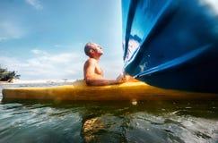 Equipaggi ritenere la luce del sole sul suo fronte quando naviga in canoa dentro Fotografia Stock