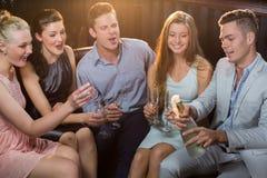 Equipaggi schioccare una bottiglia del champagne mentre amici che lo guardano fotografia stock
