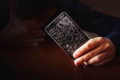 Equipaggi triste quando vedono il telefono nel fondo scuro immagini stock libere da diritti