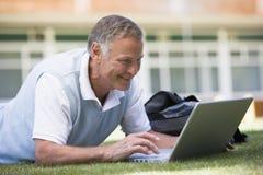 Equipaggi utilizzando il computer portatile mentre si trovano nell'erba sulla città universitaria Immagini Stock Libere da Diritti