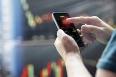 Equipaggia il telefono cellulare della tenuta della mano contro i grafici scuri del mercato azionario fotografia stock