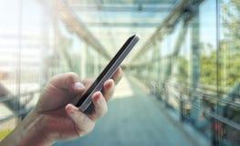equipaggia il telefono cellulare della tenuta della mano nell'edificio per uffici fotografie stock libere da diritti