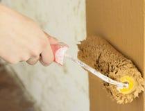 Equipaggia la mano che dipinge una parete fotografia stock