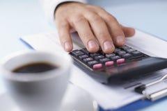 Equipaggia la mano che funziona con un calcolatore Immagine Stock Libera da Diritti