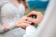 Equipaggia la mano che mette una fede nuziale sulle spose Fotografia Stock