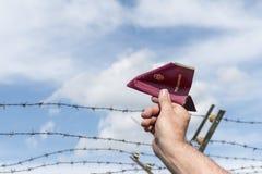 Equipaggia la mano che tiene un passaporto come aeroplano di carta sopra un pungente Fotografia Stock