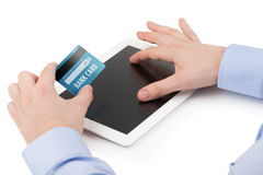 Equipaggia la mano che tiene una carta di credito sopra i comp. della compressa fotografia stock