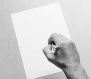 Equipaggia la mano con un foglio di carta dello spazio in bianco e della penna a sfera bianco su un fondo grigio, primo piano di  Fotografia Stock Libera da Diritti